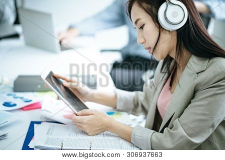 Beautiful Girl Is Working On Tablet And Listening To Music By Headphone.office Girls Relax By Listen