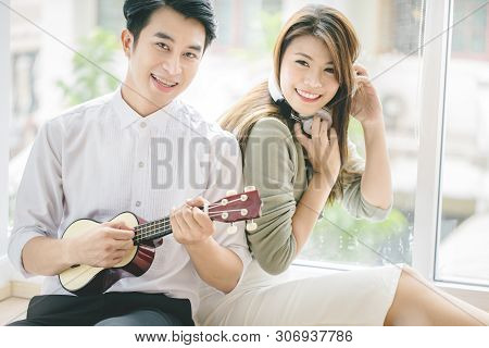 Couples Of Asian Younger Men And Women Playing Guitar With Relaxing And Happiness Emotion.
