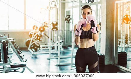 Portrait Of A Confident Young Athlete Woman Posing In Boxing Gloves.attractive Female Punching A Bag