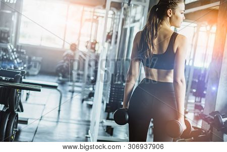 Young Girl Playing Dumbbell To Exercise In Fitness.slim Girl Lifts Heavy Dumbbell While Training In