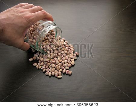 Pinto Bean Seeds Hand Dish.pinto Bean Seeds Are Poured From A Glass Jar On Brown Wooden Surface.clos