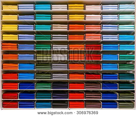 Colorful Rainbow Clothes Background .various Vibrant Color Shirts Perfectly Folded On A Shelf In The