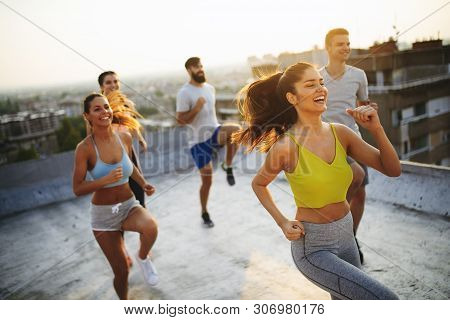 Group Of Happy Fit Young People Friends In Sportswear Doing Exercises . Sport Outdoors