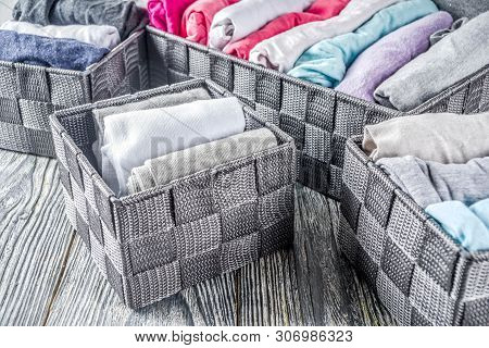 House cleaning concept. Vertical tidying up storage. Marie Kondo tidying method. Neatly folded clothes in the organizer boxes for wardrobe. Wooden background copy space above banner poster