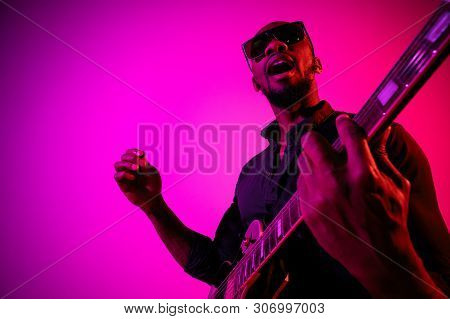 Young African-american Musician Playing The Guitar Like A Rockstar On Gradient Purple-pink Backgroun
