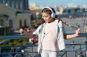 I love my pigtail hairstyle. Small child wearing braided hairstyle and headphones outdoor. Little girl with long hairstyle in casual wear. Cute kid following modern hairstyle and technology trends. poster