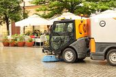 A street sweeper sweeps up a stone pavement with a strong brush in rainy weather. Maintaining clean tourist city. Preventing environmental disaster. Budget item of the city. Automation of the janitor poster