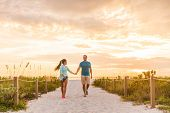 Happy young couple in love walking on romantic beach stroll at sunset. Lovers holding hands on Florida vacation holidays. People walking on summer evening lifestyle. poster