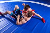 Two young man  wrestlers in red and blue uniform wrestling  on a blue wrestling carpet in the gym. Grappling. poster