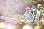 Tilt shot of happy father and son catching fish in butterfly fishing net at lakeshore poster