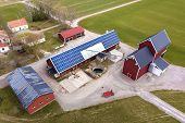 Top view of rural landscape on sunny spring day. Farm with solar photo voltaic panels system on wooden building, barn or house roof. Green field copy space background. Renewable energy production. poster