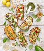 Assorted  open faced sandwiches, Open avocado sandwiches made of  slices of sourdough bread with  various toppings on a white wooden table, top view poster