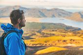 Hiker man on New Zealand trek hike tramping on outdoor trail mountain landscape. Young caucasian tramper walking with backpack at sunset nature. poster