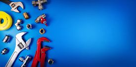 Plumbing Tools And Fittings On Blue Background With Copy Space