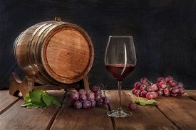 A Glass Of Red Wine With A Wine Barrel, Grapes, And Vine Leaves, On A Dark Rustic Background, Low Ke