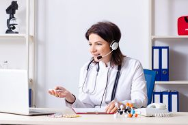 Middle-aged female doctor in telemedicine concept