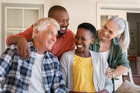 Cheerful friends sitting in courtyard enjoying afternoon together. Group of four mature people sitting outside home and laughing. Happy senior man and old woman enjoying with mature african couple.