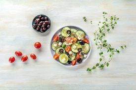 Greek Salad With Ingredients. An Overhead Photo Of A Plate Of Fresh Salad With Feta Cheese, Tomatoes