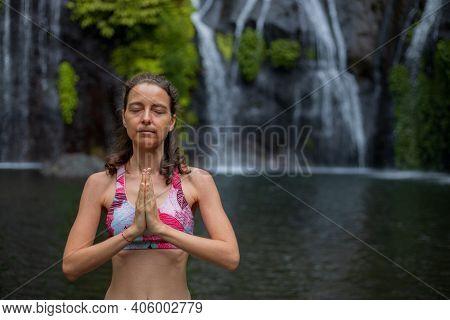 Namaste Mudra. Close Up. Yoga Near Waterfall. Young Woman Meditating, Practicing Yoga And Pranayama