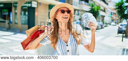 Young beautiful shopper woman smiling happy going to the shops sales holding shopping bags ourtdoors, smiling happy holding dollars bank notes