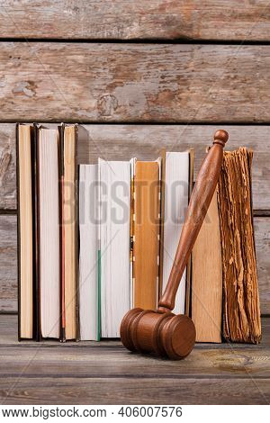 Wooden Gavel And Old Books. Vertical Shot Wooden Judge Hammer And Aged Books Vertical Shot.