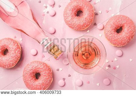 Rose wine or cocktail with pink donuts and pink chocolate beans on pink background