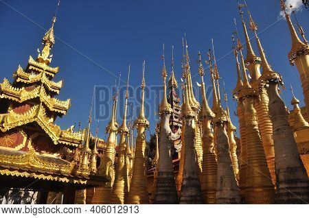 Exterior Of Exotic Temple With Stupas And Payas, From Below Shot Of Golden Bright Stupas Of Temple O