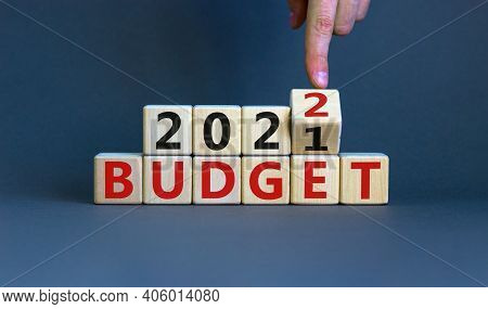 Business Concept Of Planning 2022. Businessman Flips A Wooden Cube And Changes Words 'budget 2021' T