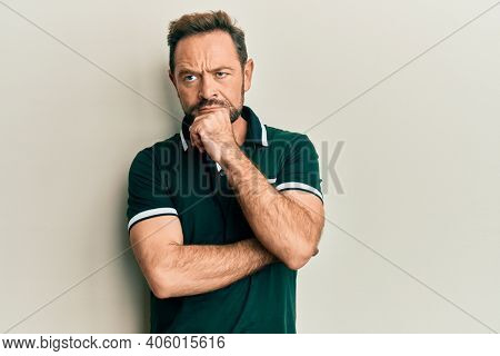 Middle age man wearing casual clothes thinking concentrated about doubt with finger on chin and looking up wondering