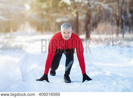 Senior Man Ready To Jog On Country Road With Snow On Cold Winter Day. Athletic Mature Sportsman Stan