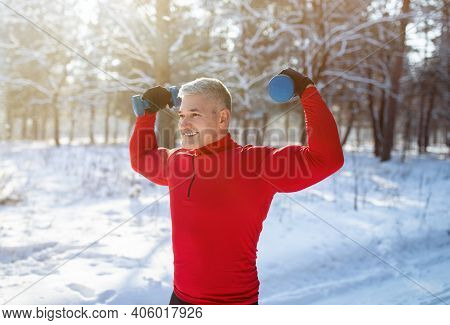 Positive Senior Man Exercising With Dumbbells Outdoors In Winter. Mature Bodybuilder Working Out His