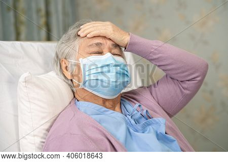 Asian Senior Or Elderly Old Lady Woman Patient Wearing A Face Mask And Headache New Normal In Hospit