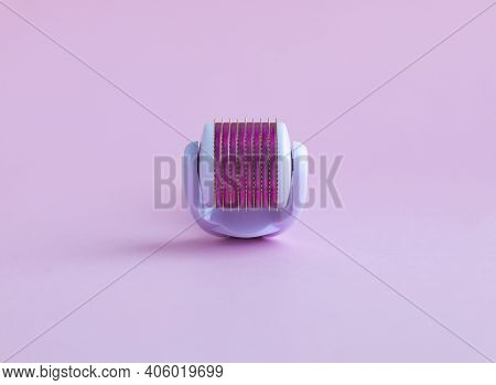 Cosmetic Device For The Regeneration Of Skin Cells Mesoscooter Close-up On A Pink Background.