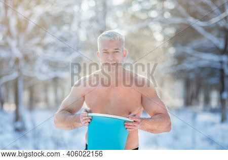 Handsome Senior Man With Bare Chest Holding Bucket Of Chilly Water Outdoors In Winter. Attractive Ma