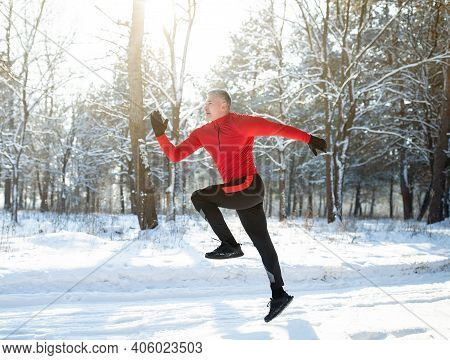 Full Length Portrait Of Strong Mature Sportsman Jogging Outside In Sunny Winter Park, Side View. Sen