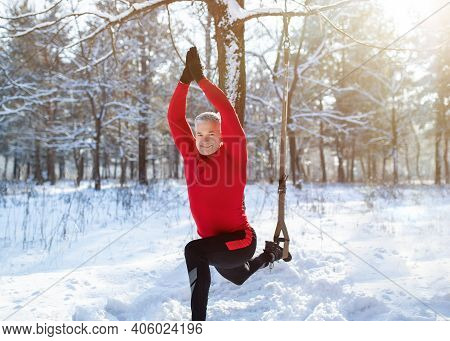 Outdoor Winter Fitness Concept. Sporty Senior Man Training With Trx Resistance Straps At Snowy Fores
