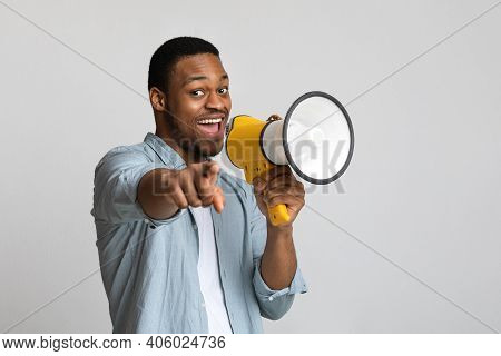 Positive African American Guy Shouting In Megaphone And Pointing At Camera Over Grey Background, Cop