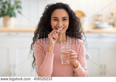 Beauty Supplement. Smiling Brunette Woman Taking Vitamin Pill And Drinking Water At Home, Attractive