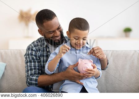 Financial Literacy. Cheerful African Father And Son Putting Money In Piggybank Sitting On Sofa At Ho