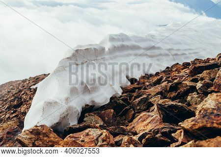 Large Snowy Dome On Mountain Top Close-up. Firn On Stony Mountain Peak On Background Of Clouds. Snow