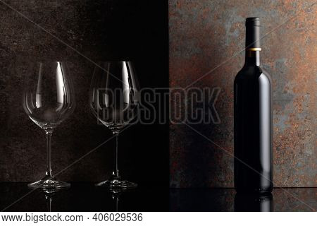 Bottle Of Red Wine With Empty Wine Glasses On Rusty Brown Background. Frontal View With Space For Yo