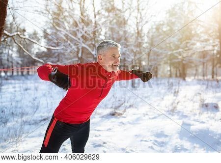 Winter Sports Concept. Handsome Senior Man Training With Fitness Straps At Snowy Forest, Copy Space.