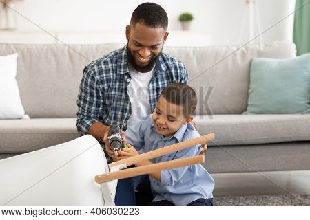 Happy Black Father And Son Fixing Table Working Doing House Chores Together At Home. Household Chore