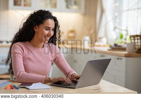 Remote Work. Beautiful Young Freelancer Lady Working With Laptop In Kitchen, Happy Millennial Woman