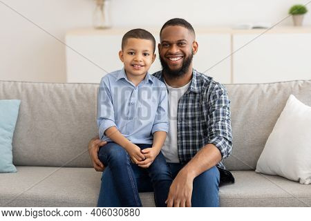 Portrait Of Happy Black Father And Son, Little Boy Sitting On Dads Knees Smiling To Camera At Home.