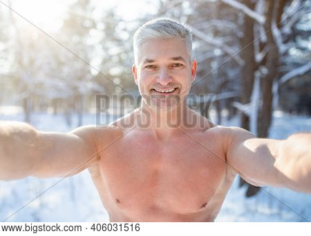 Positive Senior Man With Bare Chest Taking Selfie At Snowy Winter Forest. Cheerful Mature Guy Taking
