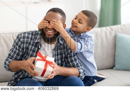 Dads Birthday. Little Son Congratulating Black Father Giving Wrapped Gift To Him, Covering Eyes Sitt