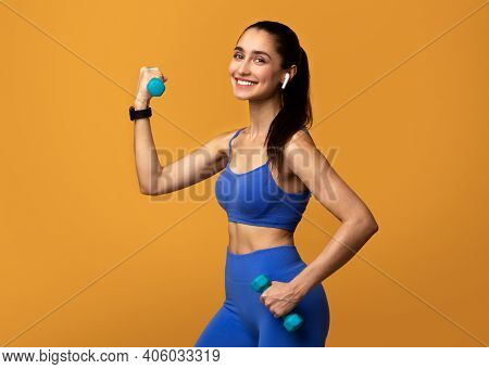 Strength Workout Concept. Portrait Of Smiling Fit Lady Exercising With Two Dumbbells, Wearing Wirele