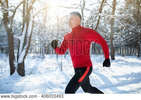 Senior Athletic Man In Sportswear Running At Winter Park, Copy Space. Mature Male Runner Training Ou