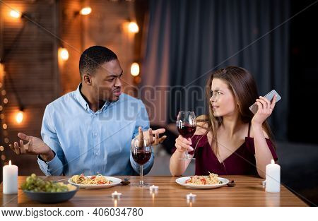 Annoyed Black Guy Arguing With His Girlfriend Busy With Cellphone On Date In Restaurant. Young Multi